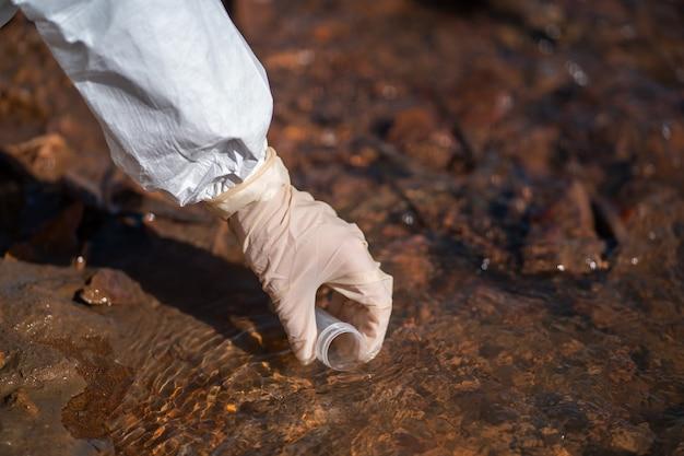 Científico o biólogo con uniformes protectores trabajando juntos en el análisis del agua.