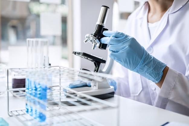Científico o médico en bata de laboratorio trabajando en laboratorio de biotecnología