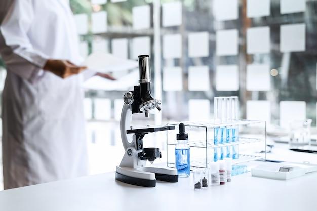 Científico o médico en bata de laboratorio con tubo de ensayo con microscopio