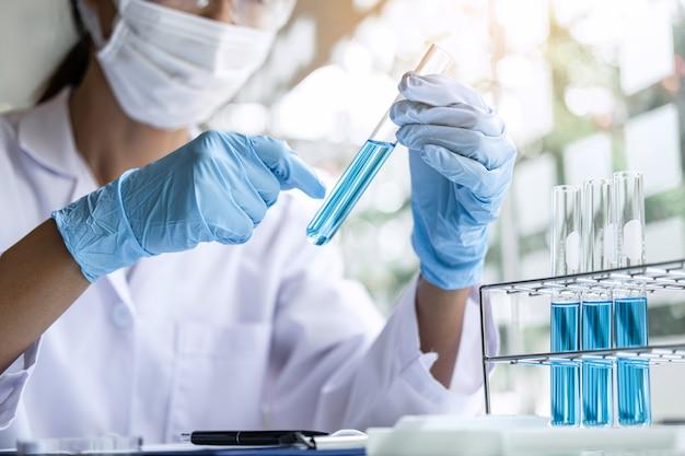 Científico o médico en bata de laboratorio con tubo de ensayo con reactivo