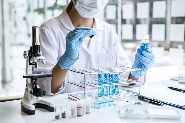 Científico o médico en bata de laboratorio con tubo de ensayo