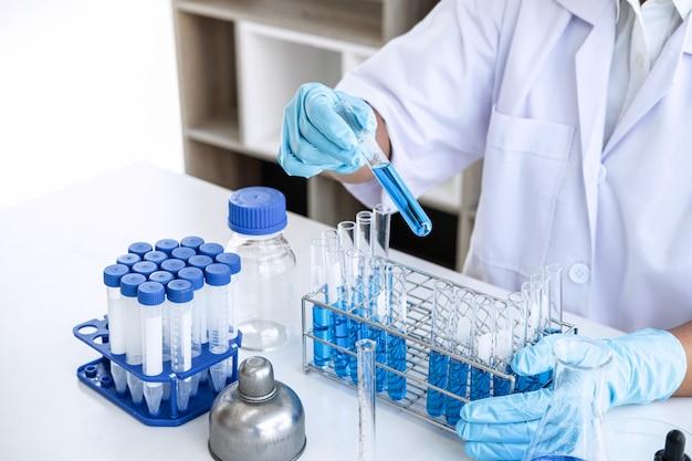Científico o médico en el laboratorio que trabaja en el laboratorio de biotecnología utilizando equipos para la investigación con mezcla de reactivos en frascos de vidrio en laboratorio clínico