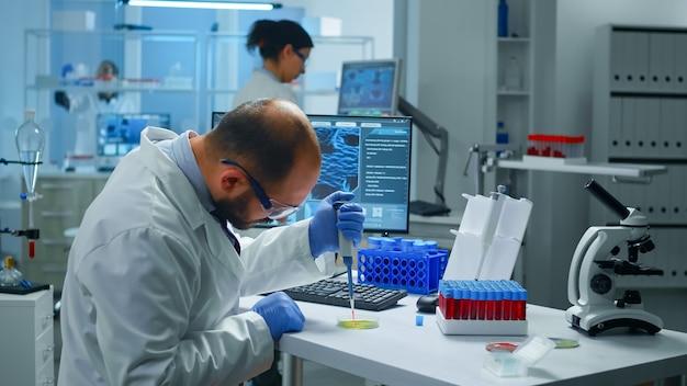 Científico poniendo muestra de sangre del tubo de ensayo con micropipeta en placa de petri analizando la reacción química