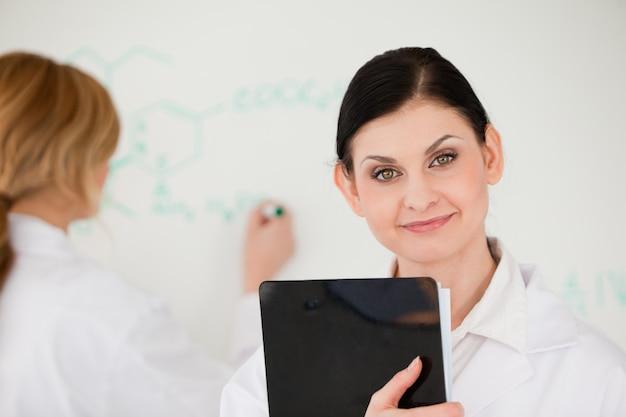 Científico posando mientras que otro está escribiendo una fórmula en una pizarra