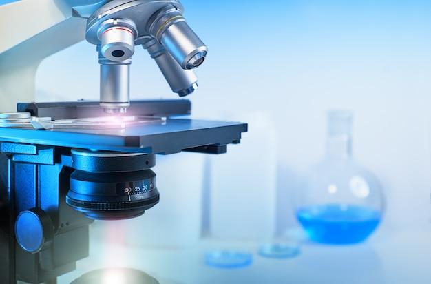 Científico con primer plano en microscopio óptico y laboratorio fuera de foco
