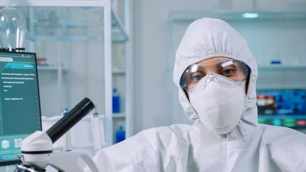 Científico profesional de la mujer en traje de protección mirando cansado a la cámara en el laboratorio equipado. equipo con exceso de trabajo que examina la evolución del virus utilizando alta tecnología y herramientas para el desarrollo de vacunas de investigación científica