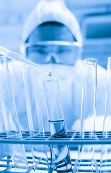 Científico protegido cayendo líquido peligroso en un tubo de ensayo