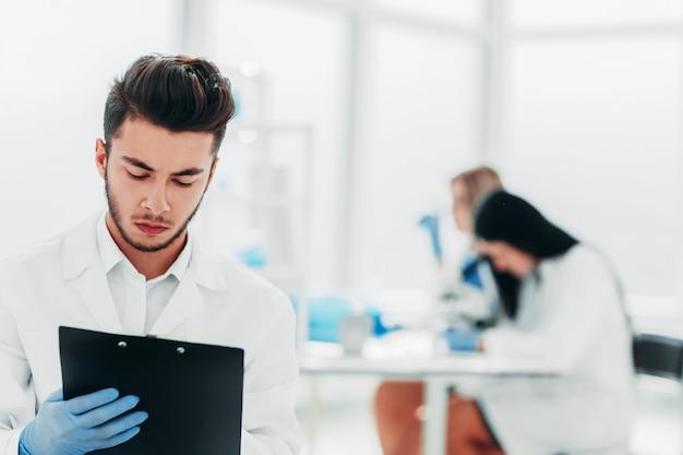 Un científico que hace escribe los resultados de un experimento en una revista de laboratorio.