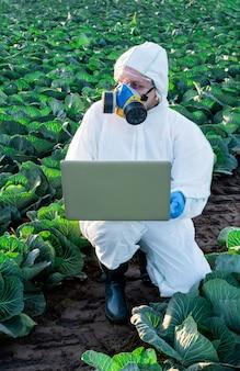 El científico que lleva un equipo de protección blanco, una máscara química y gafas utiliza una computadora portátil en el campo agrícola.