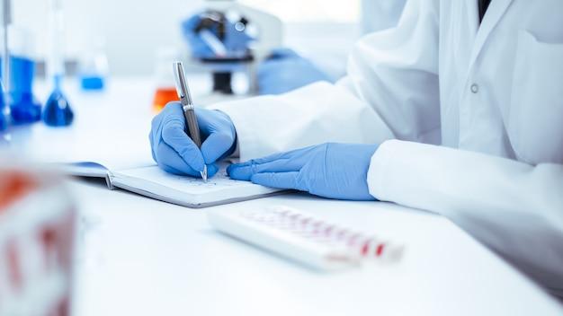 Científico que registra los resultados del estudio en una revista de laboratorio