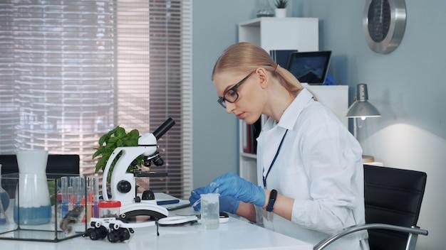 Científico de química examinando sustancia bajo lupa