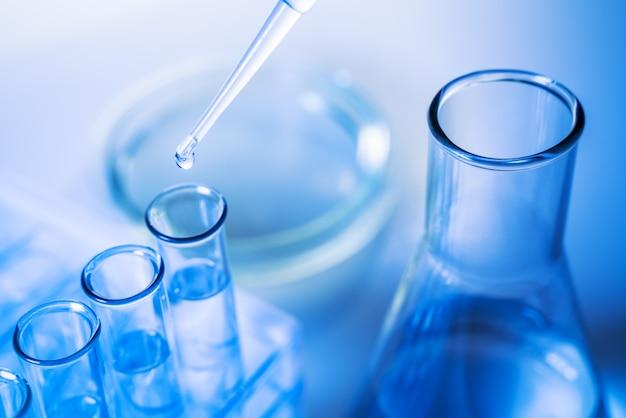 Un científico realiza un experimento en un laboratorio. equipos para experimentos químicos. técnico de laboratorio vierte un reactivo en un tubo de ensayo.