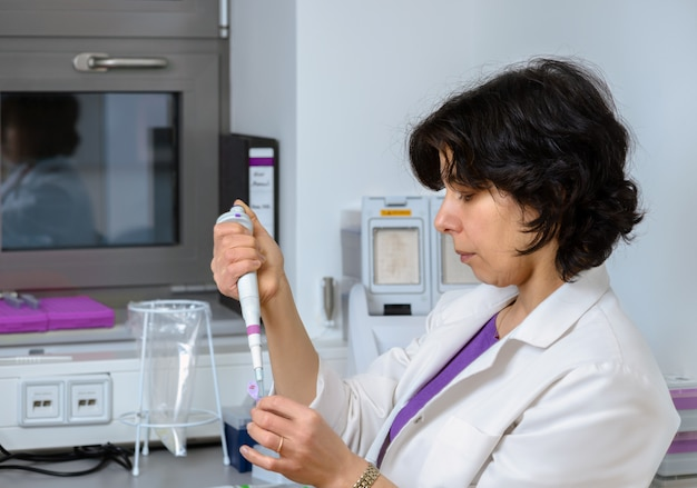 Científico senior trabaja con pipeta automática