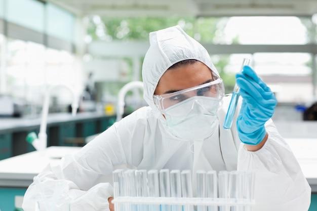 Científico de sexo femenino protegido que mira un tubo de prueba