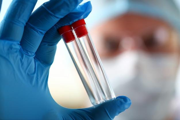 Científico de sexo masculino mantenga en brazo frascos vacíos closeup