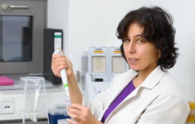 Científico superior trabaja con pipeta automática.