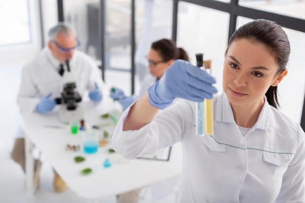 Científico de tiro medio sosteniendo tubos