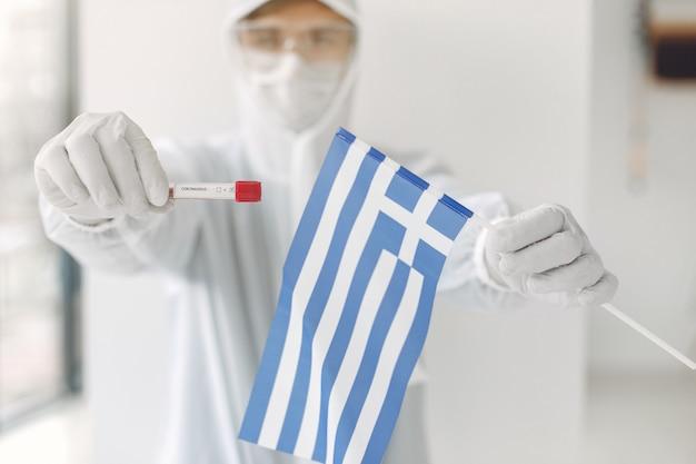 El científico en traje de overol con una muestra de coronavirus y una bandera griega
