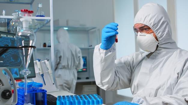 Científico en traje de química estéril analizando la muestra de sangre del tubo de ensayo. investigador de viorolog en un laboratorio profesional que trabaja para descubrir un tratamiento médico contra el virus covid19.