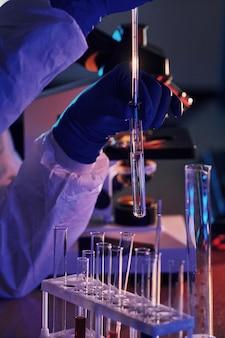 Científico en uniforme protector blanco trabaja con coronavirus y tubos de sangre en laboratorio