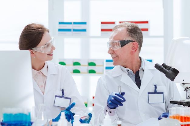 Científicos discutiendo muestras sentados en una mesa de laboratorio