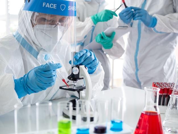 Científicos y microbiólogos sostienen un tubo de ensayo con sangre recolectada de pacientes