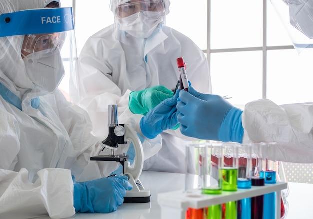 Científicos y microbiólogos sostienen tubos de ensayo con sangre recolectada de pacientes.