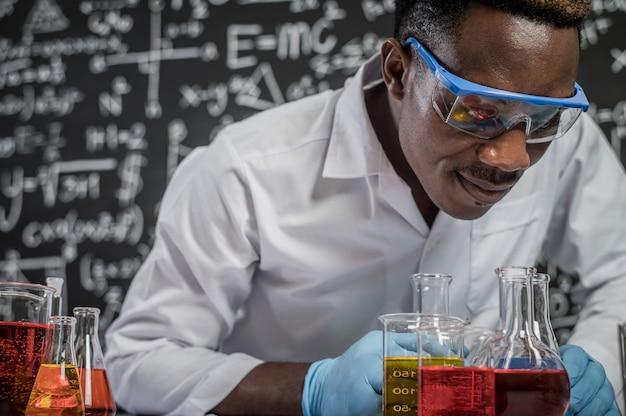 Los científicos observan los químicos en el vidrio en el laboratorio.