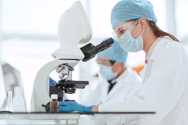 Científicos que prueban el líquido y escriben los resultados en un diario de laboratorio