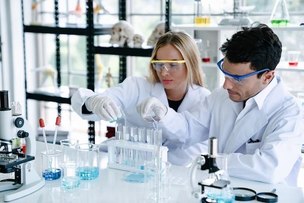 Científicos que realizan pruebas con un tubo de ensayo mientras realizan investigaciones en un laboratorio de ciencias.