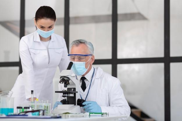 Científicos que trabajan con microscopio.