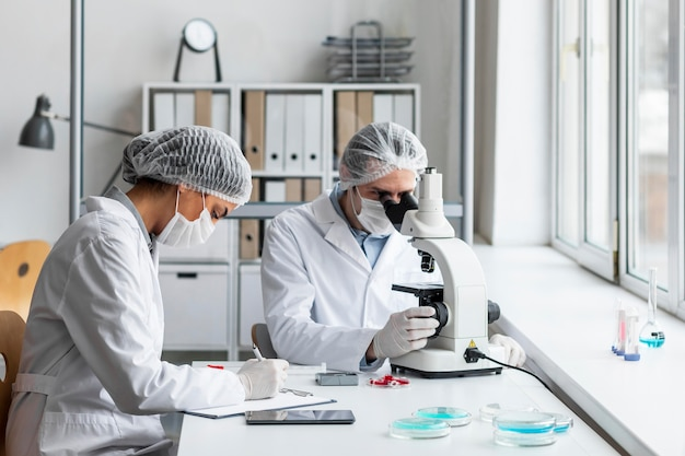 Científicos de tiro medio en laboratorio