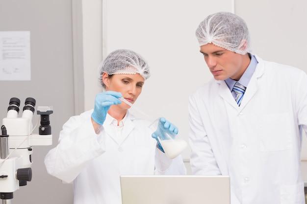 Científicos trabajando atentamente con vaso de precipitados
