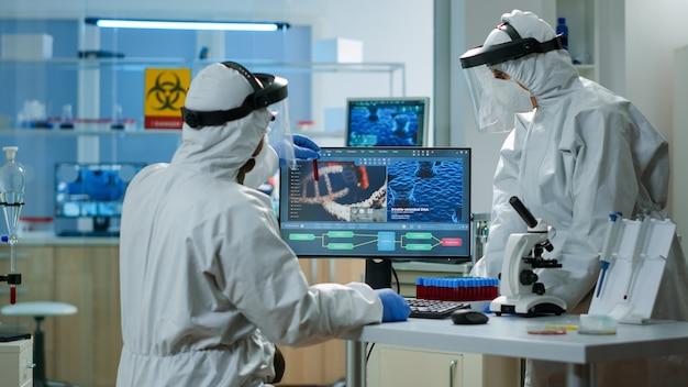 Científicos en trajes de protección analizando tubos de ensayo con muestra de sangre en laboratorio equipado con productos químicos. biólogos que examinan la evolución de las vacunas utilizando alta tecnología y tratamiento de investigación de tecnología
