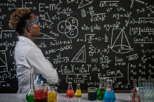 Los científicos usan anteojos y cruzan los brazos para ver la fórmula en el laboratorio