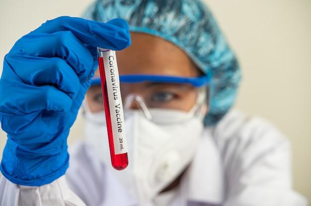 Los científicos usan guantes y sostienen vasos de precipitados.