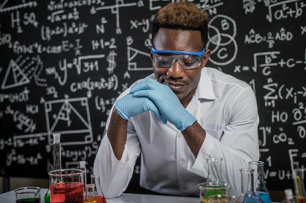 Los científicos usan ideas y miran químicos en el laboratorio