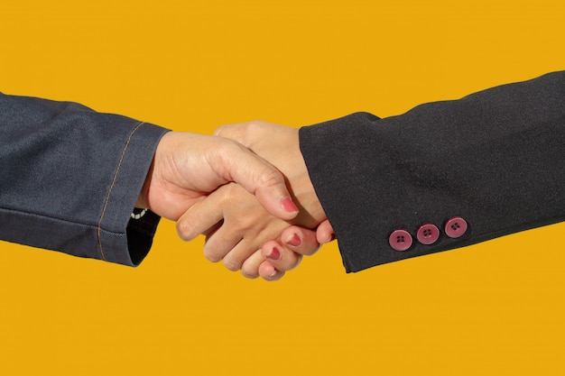 Cierre para arriba del aislante del apretón de manos del negocio en blackground amarillo