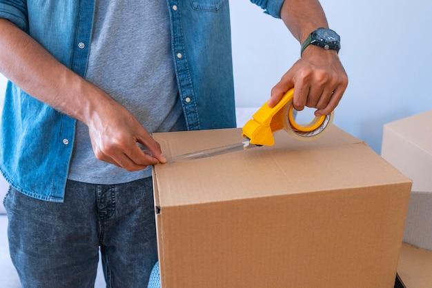 Cierre para arriba de la caja de cartón del embalaje de la mano masculina