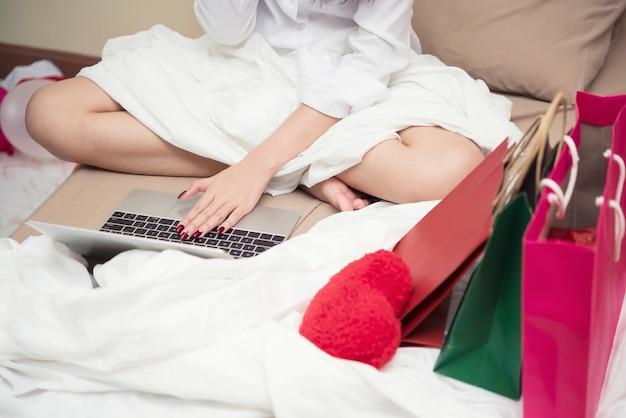 Cierre para arriba del concepto en línea del funcionamiento, de las compras y del pago de la mujer joven.