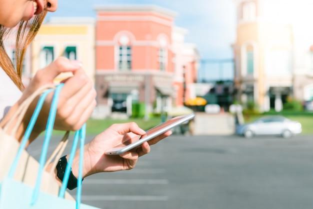 El cierre para arriba de una mujer joven sostiene bolsos de compras en su mano y charla en su teléfono después de hacer compras