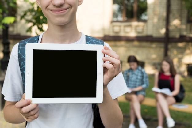 Cierre para arriba de la tableta de la tenencia del muchacho de la high school secundaria en manos