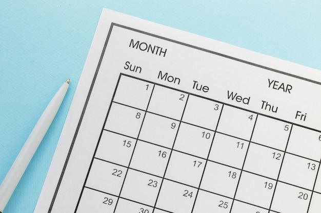 Cierre el bolígrafo y el escritorio del calendario mensual para el organizador. plan o recordatorio sobre fondo azul.