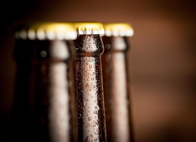 Cierre de botella de cerveza con gotas sobre fondo oscuro
