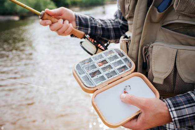 Cierre de caja de madera con diferentes tipos de silicona artificial, moscas de pesca y cebos. el hombre lo sostiene en una mano y tiene la vara en la otra. lleva chaleco y está parado en el agua.