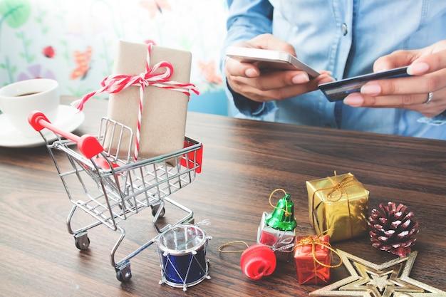 Cierre de caja de regalo y decoraciones de navidad en carrito de la compra con la mano de la mujer en línea de pago en el fondo