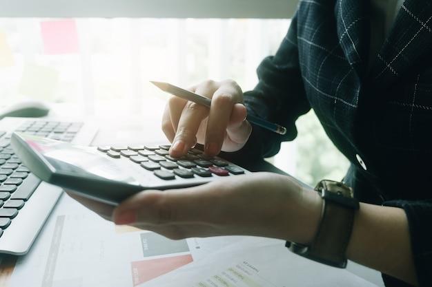 Cierre de mujer de negocios con calculadora para hacer las finanzas matemáticas en el escritorio de madera en la oficina