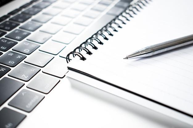Un cierre encima de la foto de una pluma colocada en un cuaderno y una computadora.