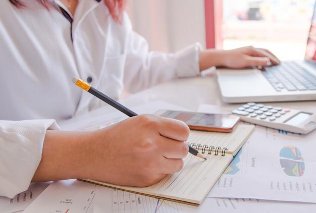 El cierre encima de la mano de la mujer usando la calculadora y la escritura hacen la nota con calcula sobre oficina del costo en casa.