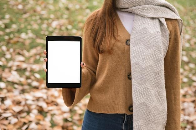 Cierre encima de la tableta de la tenencia de la mujer joven a disposición